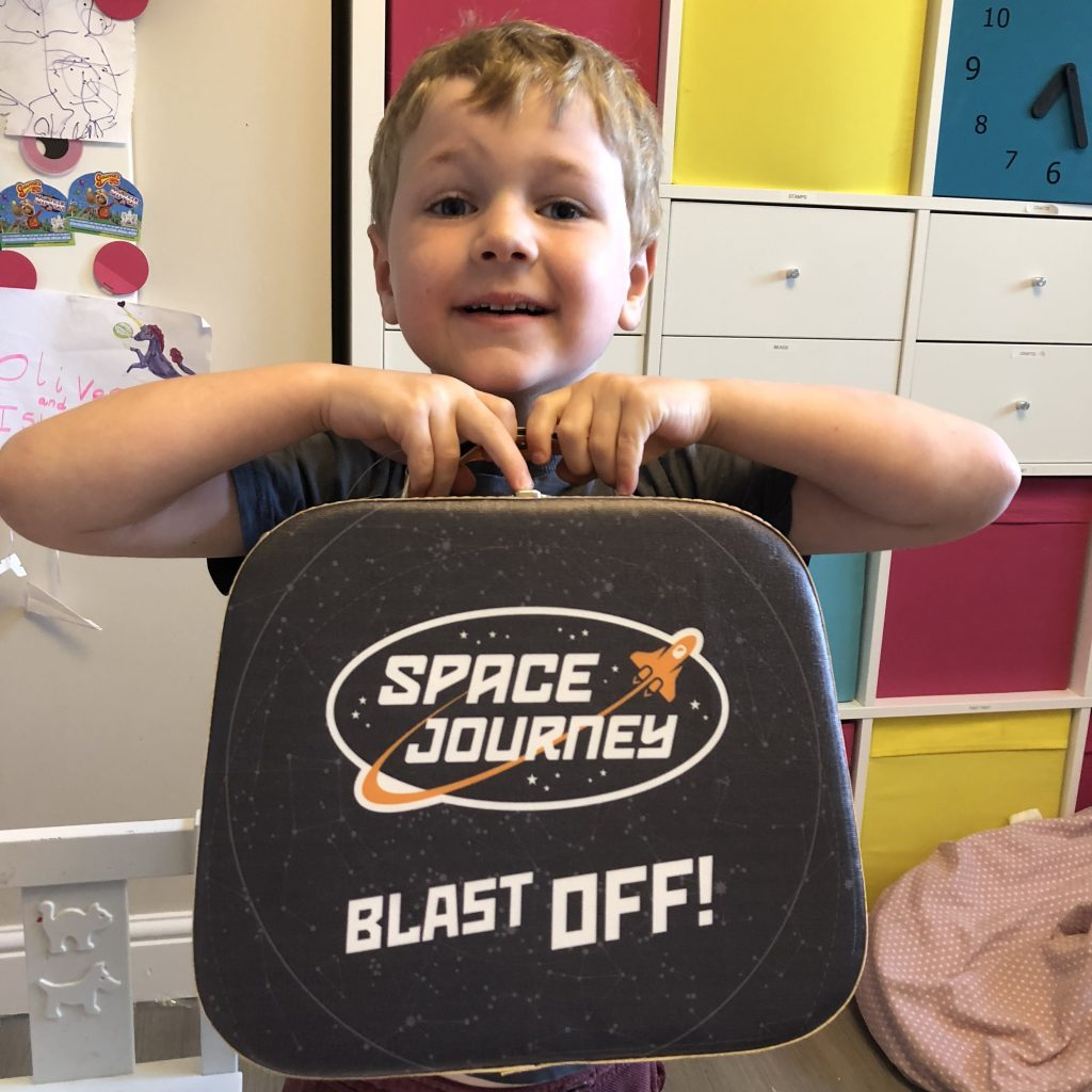 Oliver holding his new space journey suitcase