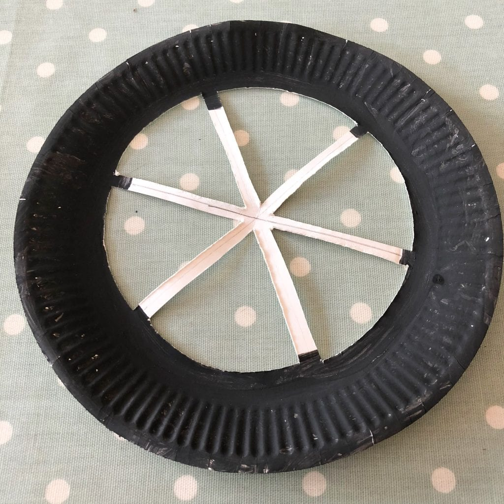 Paper plate with 6 sections cut out to make the spokes of the wheel