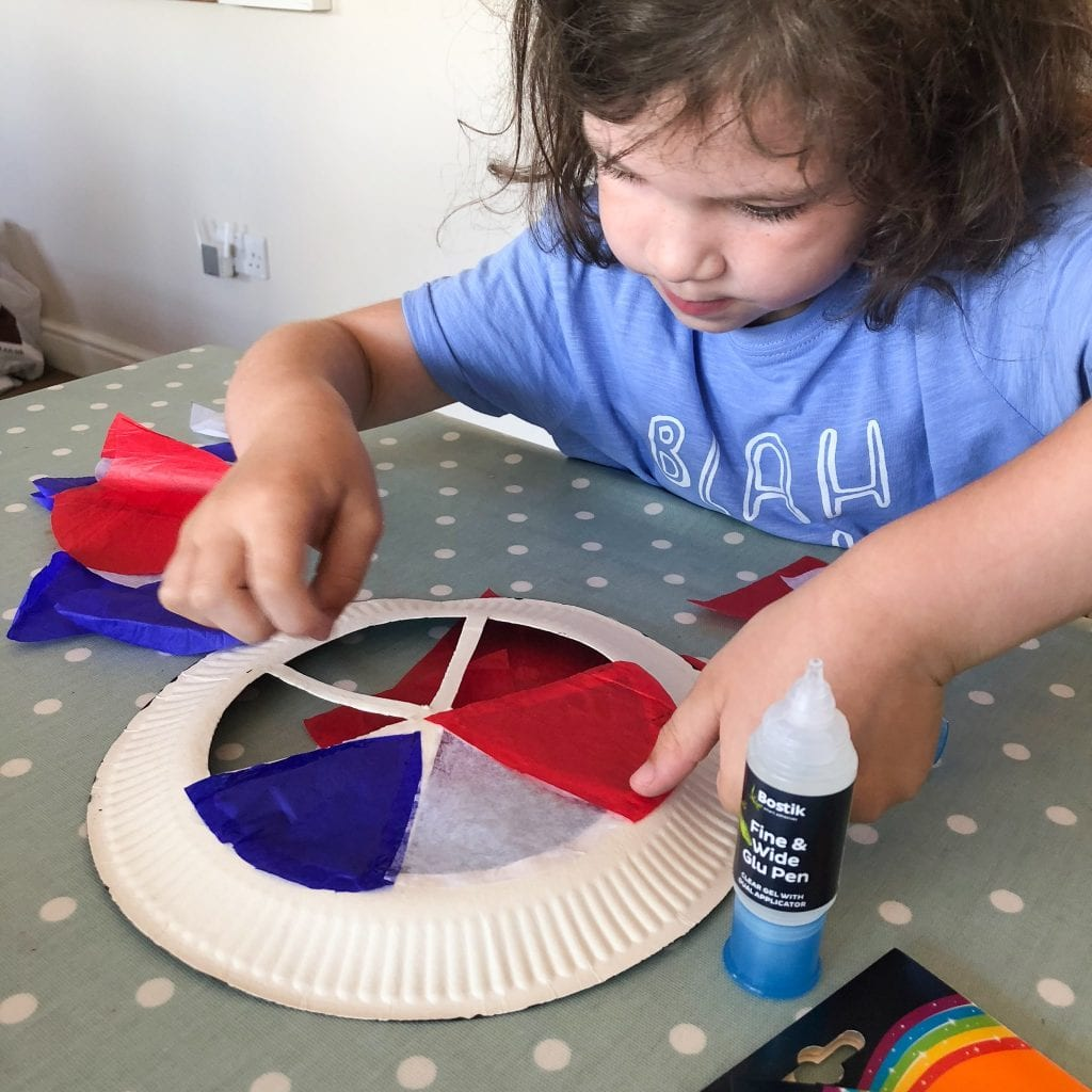 Isla sticking tissue paper in the colours of the french flag to her plate