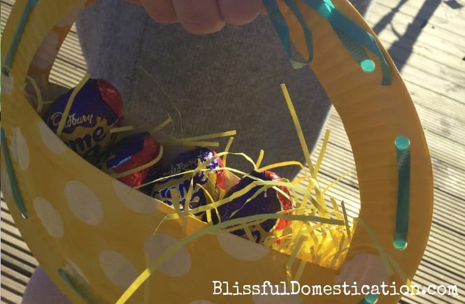 Paper plate easter basket filled with starw and chocolate eggs