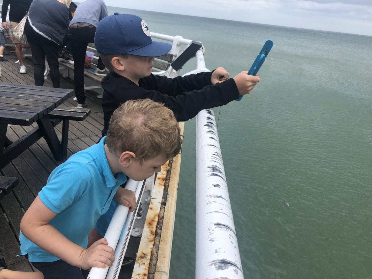Two boys crabbing off the side of cromer pier