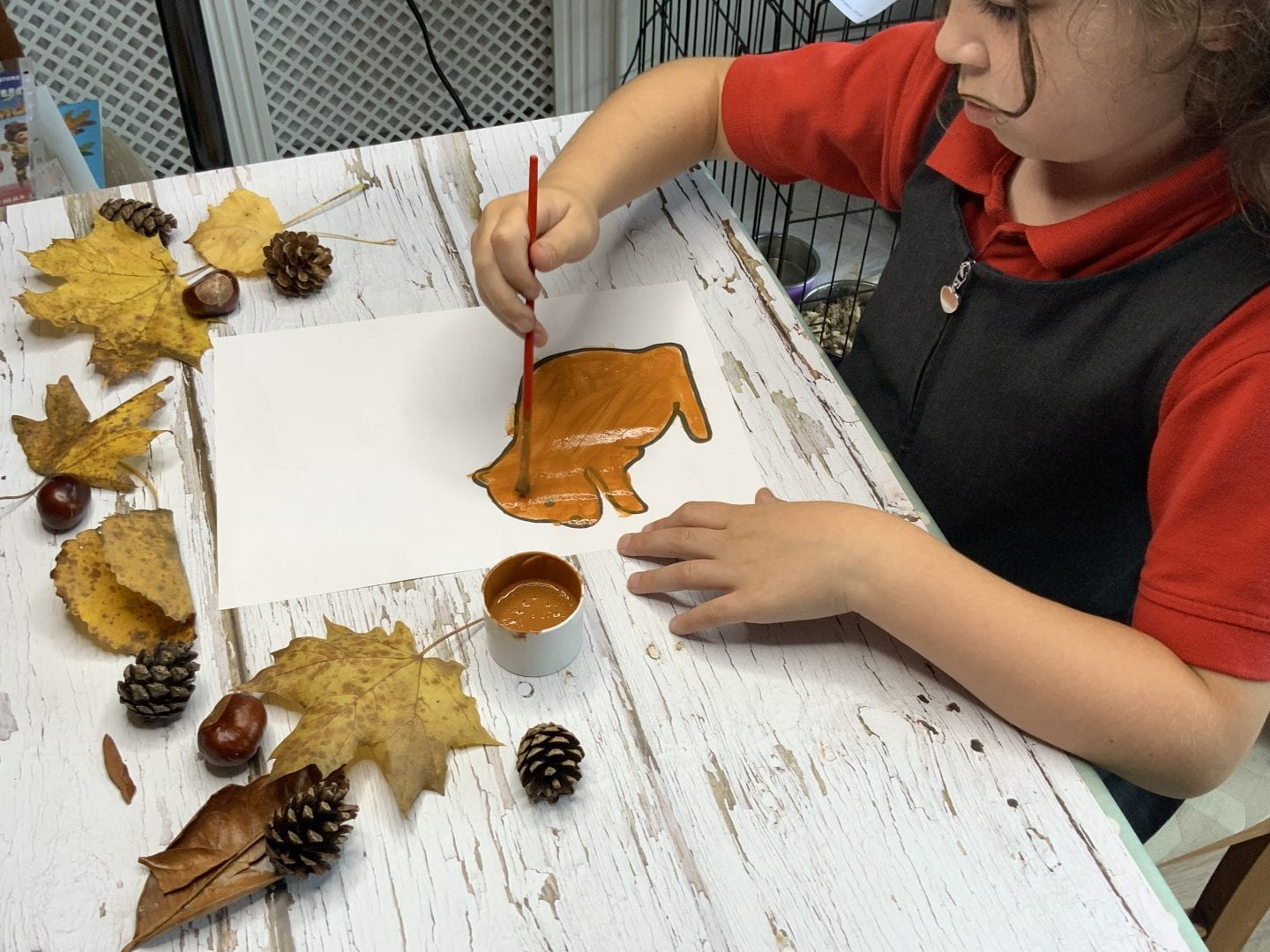 Isla painting the squirrel template before attaching the leaves