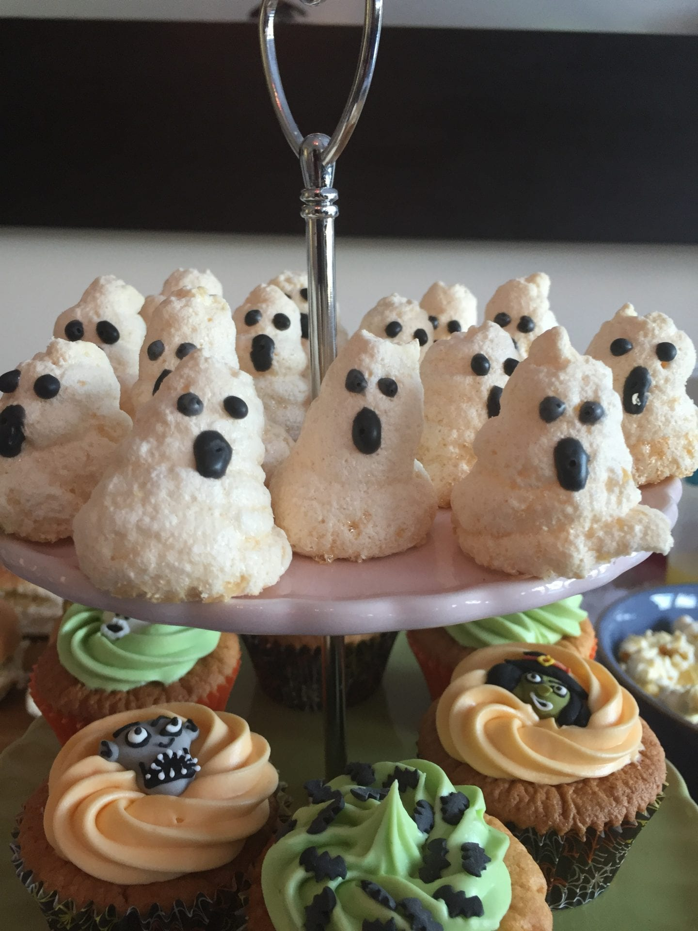 Ghost shaped meringues with black icing features