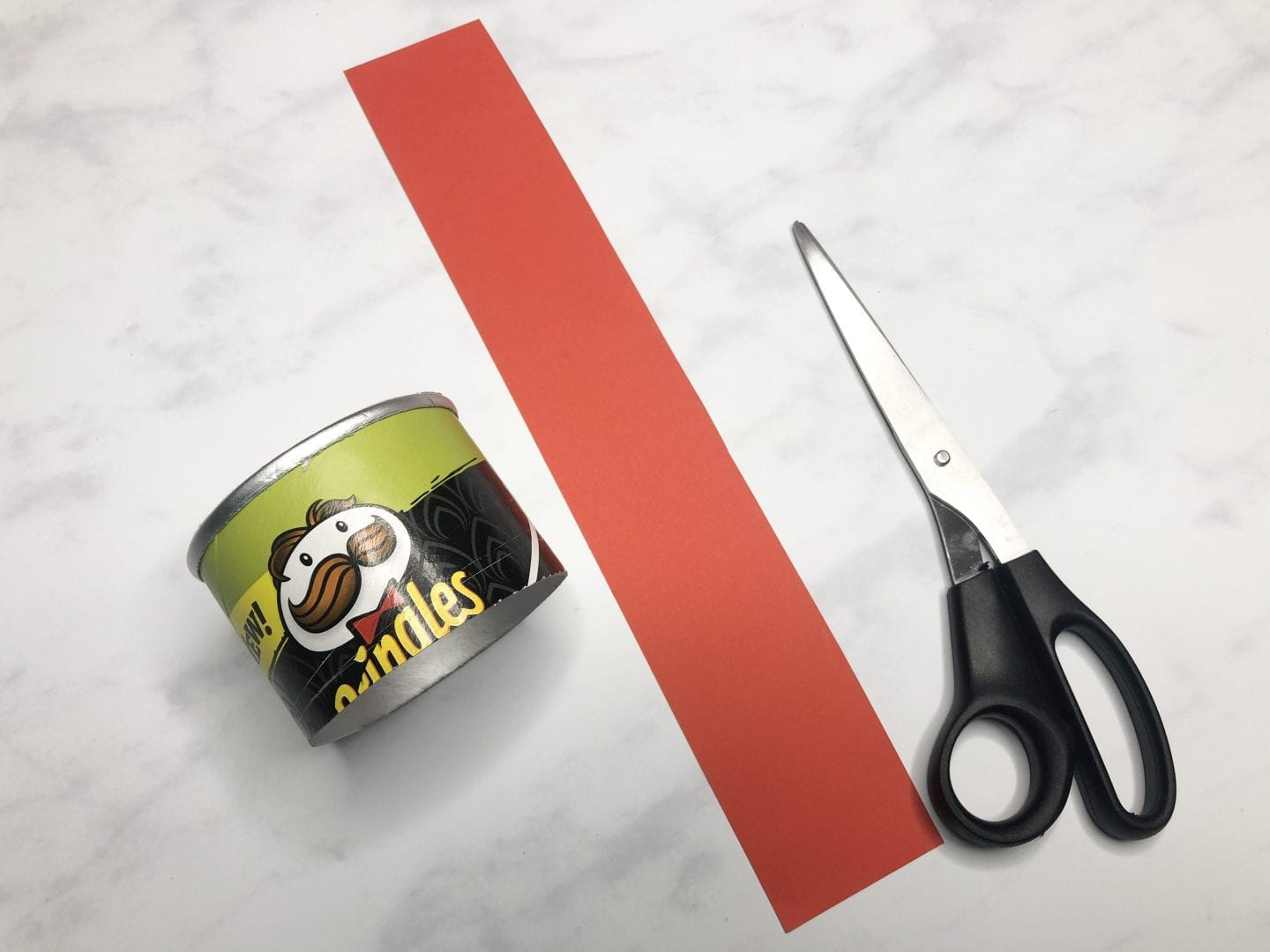 A section of the pringles tube cut with a length of red card
