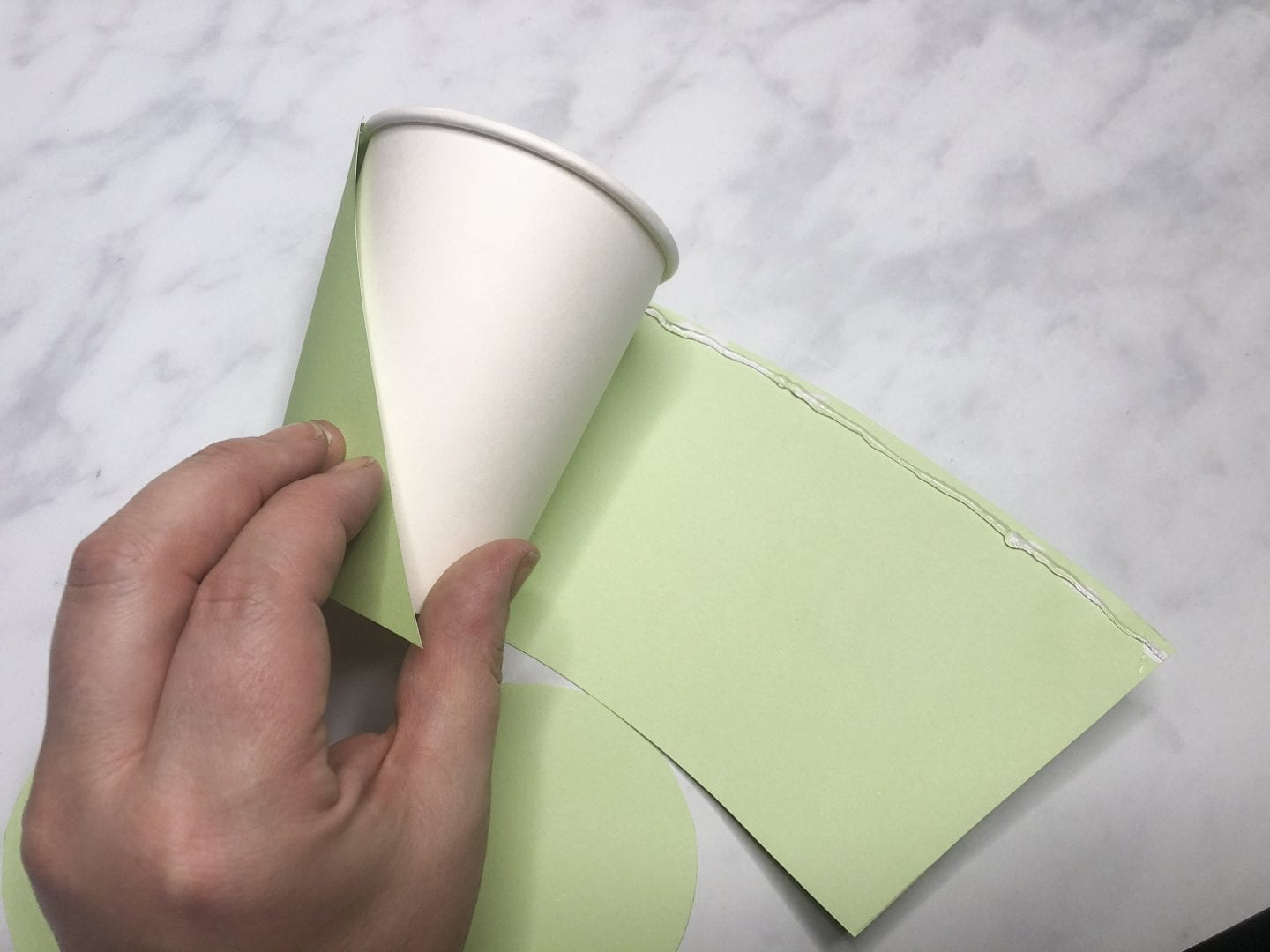 sticking the card shapes to the paper cup to cover it.