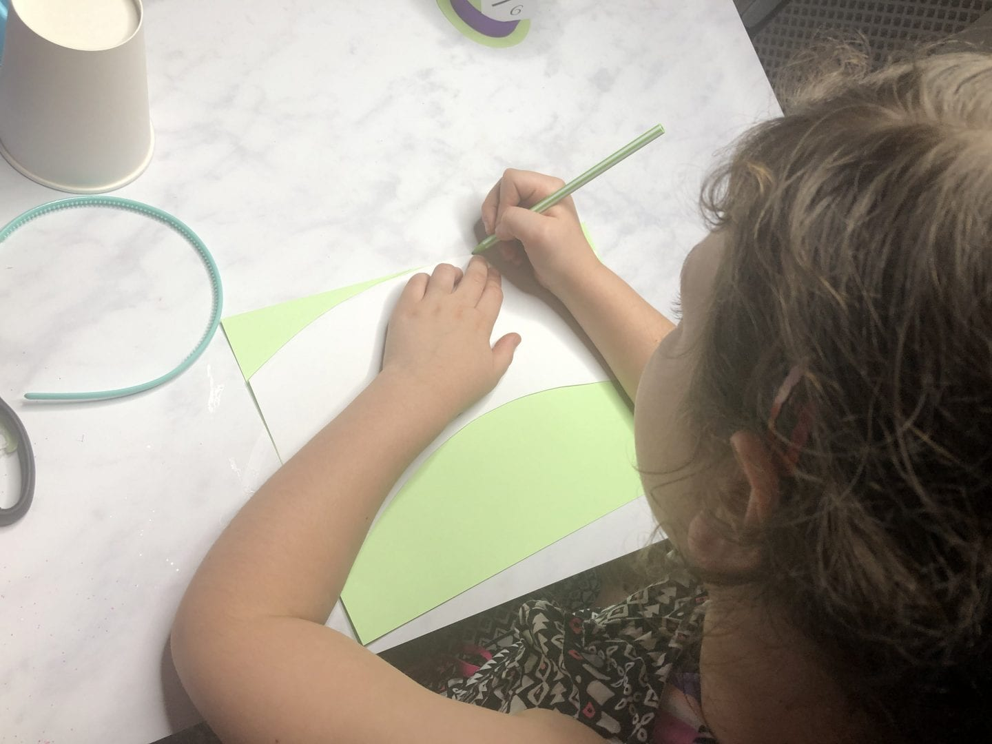 A young girl drawing around the paper template onto the sheet of coloured card.