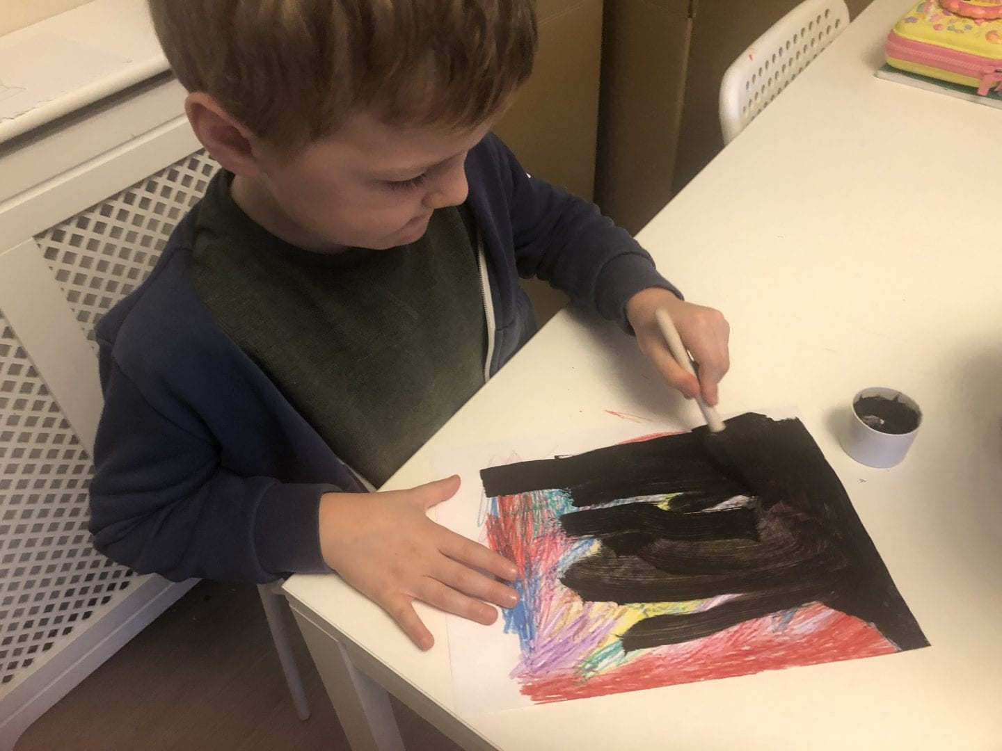 Painting the black paint mix over the sheet of paper that has been coloured in with crayons
