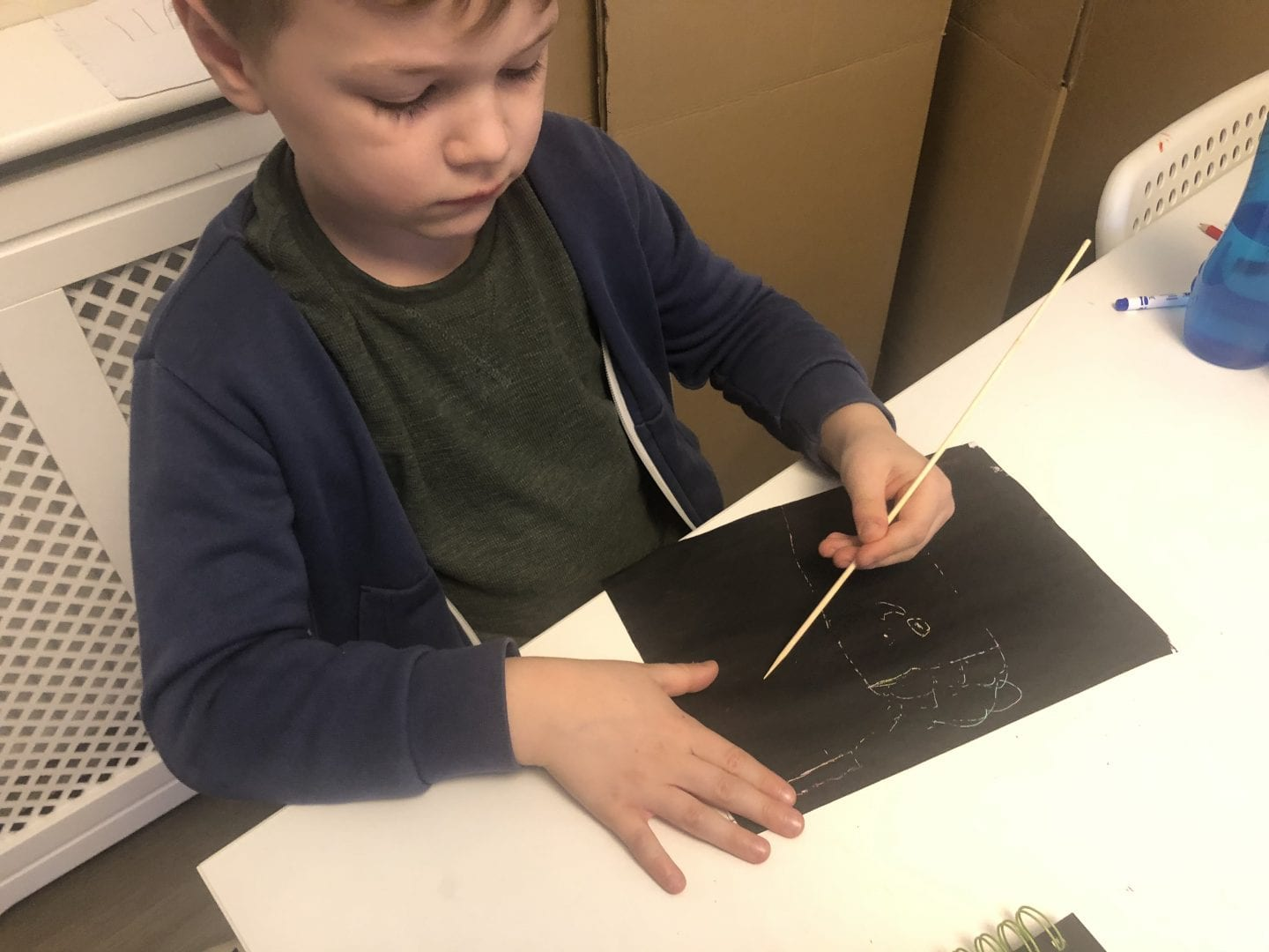 Young boy using a wooden skewer to create his scratch art
